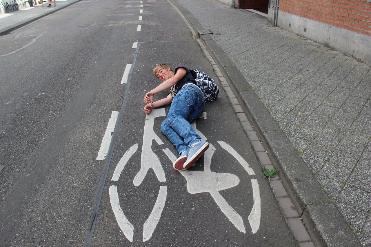 man lying on the road pretending to ride the cycle painted on the cycle lane